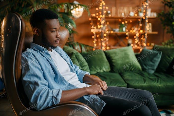 Schwarzer Mann sitzt in einem bequemen Lederstuhl