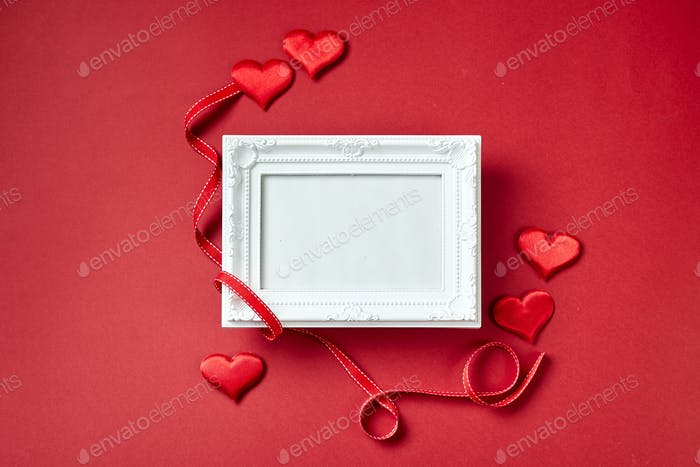 Photo frame and Valentines day hearts and decorations on red background