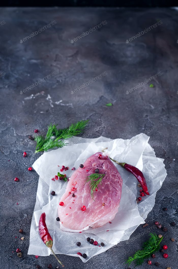 Raw fresh meat steak with spices and pepper on a dark concrete background. Food   pork .
