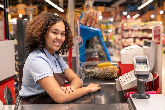 Pretty young sales clerk in apron sitting by cash register in supermarket