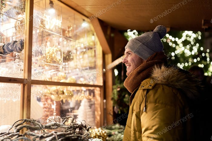 happy man looking at christmas market shop window
