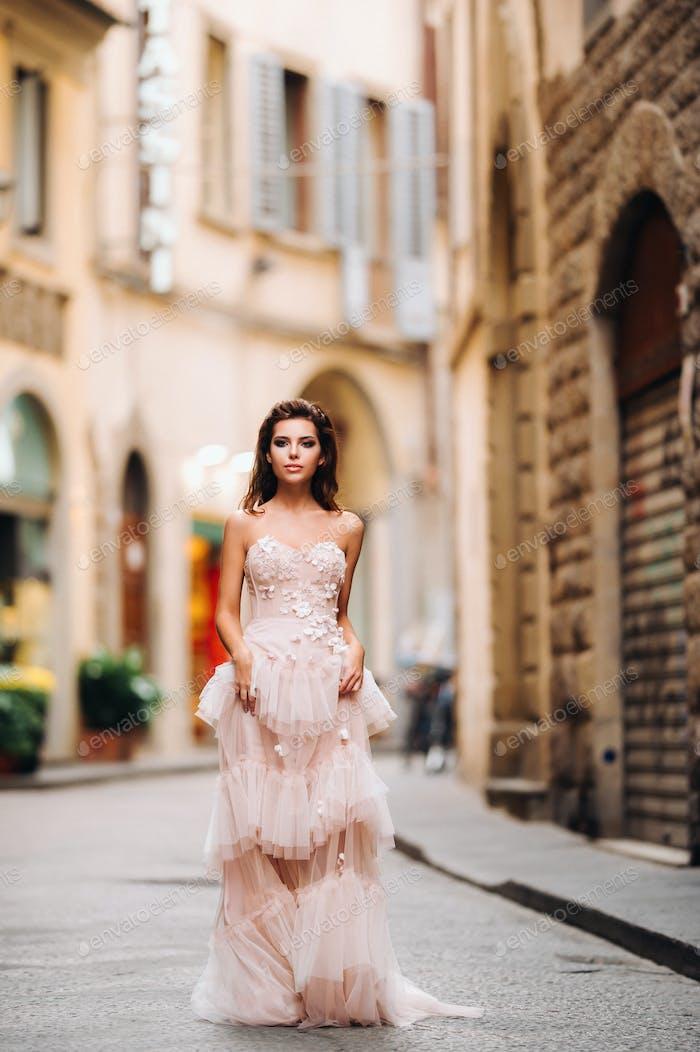 schöne stilvolle Mädchen Modell in einem rosa Hochzeitskleid in Florenz fotografiert, hält eine ungewöhnliche