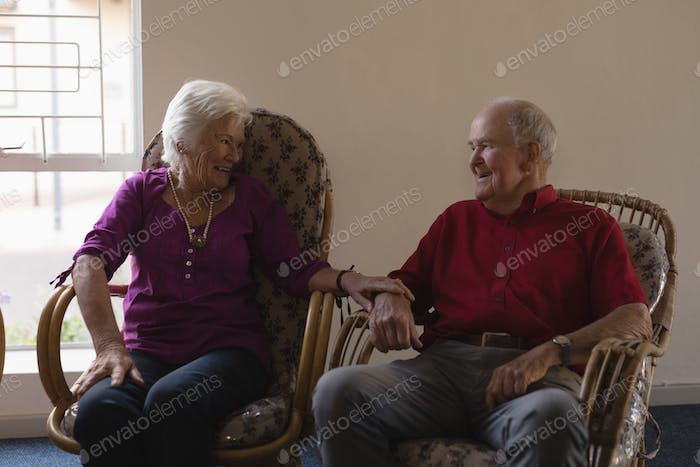 Front view of happy senior couple interacting with each other at nursing home