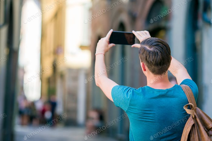 Tourist man taking photo by smartphone in hands walking along the narrow italian streets in Europe