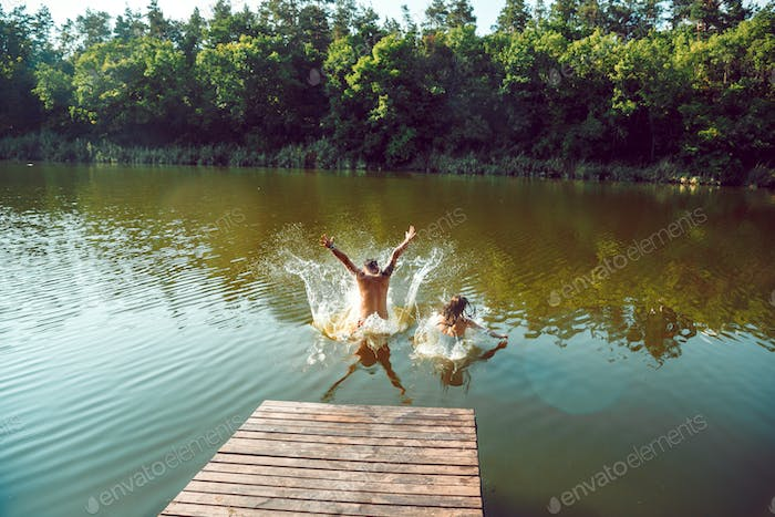 Happy friends having fun, jumping and swimming in river