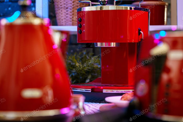 Red coffee machine on kitchen table close up