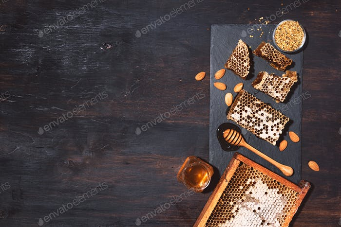 Honeycomb, bee pollen granules, honey jar with wooden dipper, almond nuts on black slate tray over