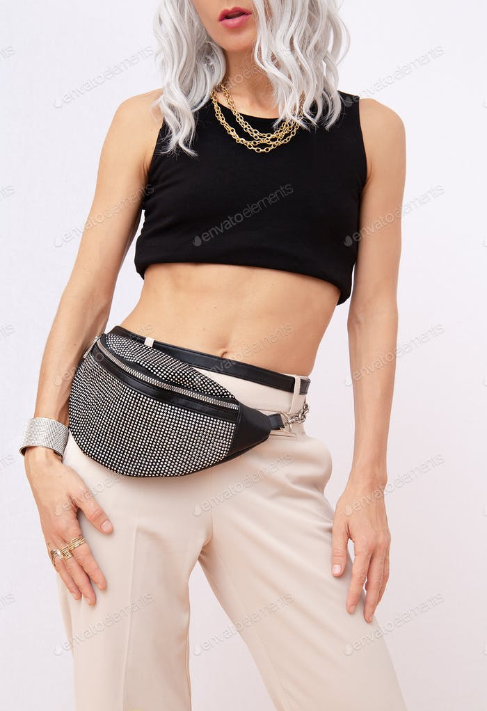 Transgender Woman fashion portrait  in stylish casual Spring summer outfit.  Clutch and jewellery.