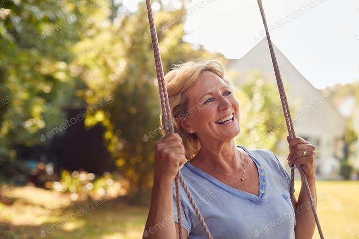 Carefree Smiling Retired Woman Having Fun On Garden Swing