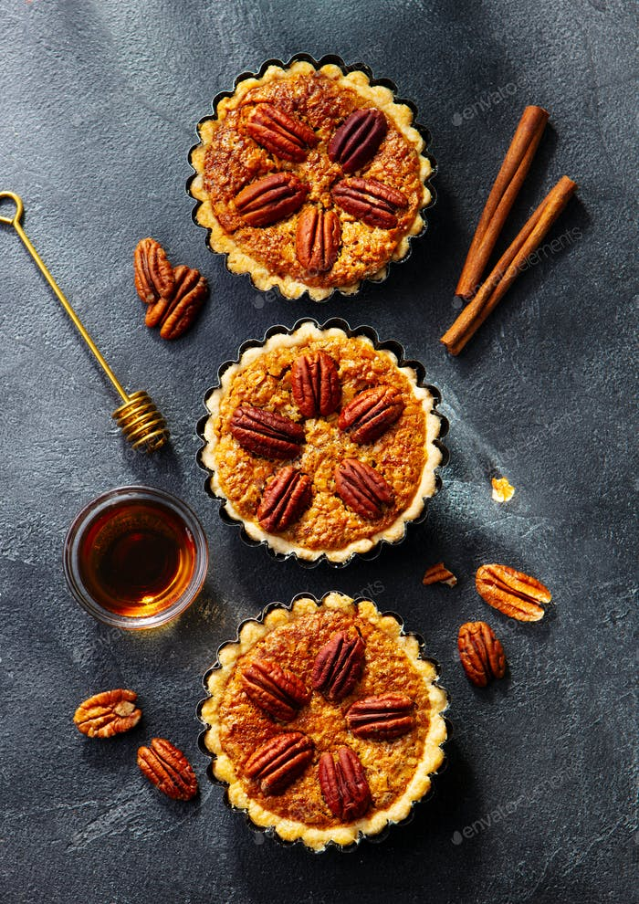 Pecan Pies, Mini Tarts. Traditional Thanksgiving Dessert. Dark Background. Top view.
