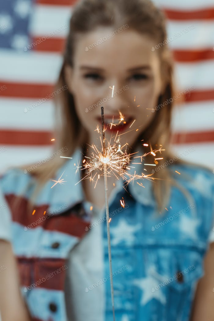 hipster girl in american patriotic outfit holding sparkler with us flag on background, 4th july -