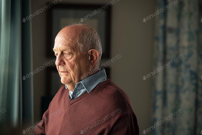 Upset senior man near window