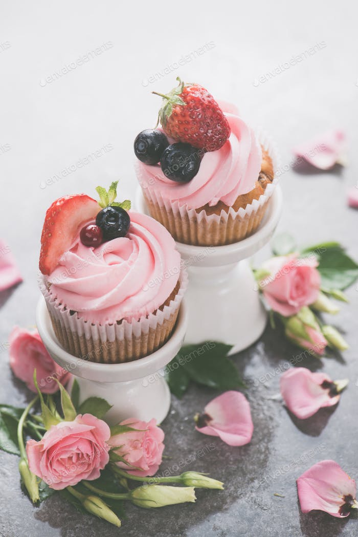 Cupcakes with on porcelain stands with rose flowers on a white background. Spring dessert concept