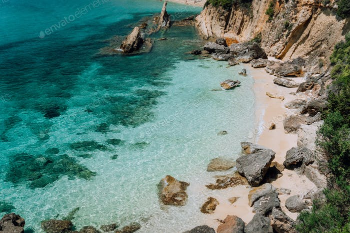 Hidden empty beach with pure clear turquoise sea water near white rock cliffs located in famous