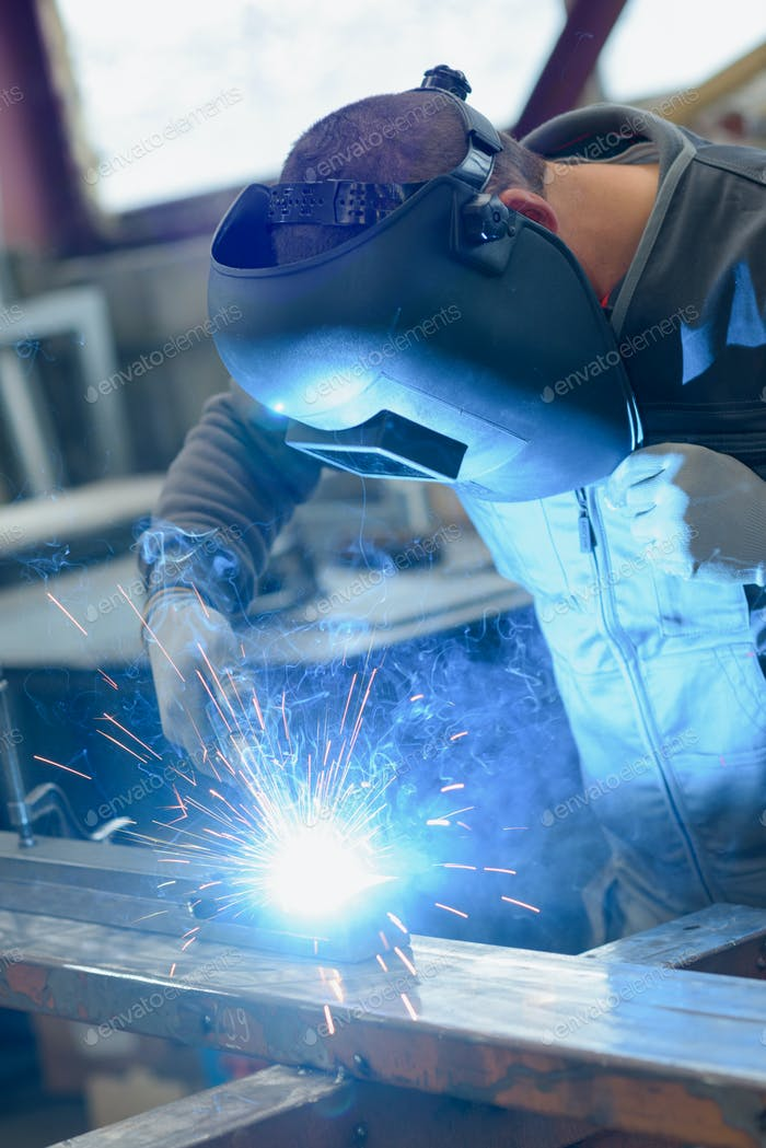 welder working in manufacture production plant
