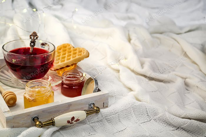 Winter concept with knitted blanket and hot tea with waffer, jam, honey on wooden tray on te bed