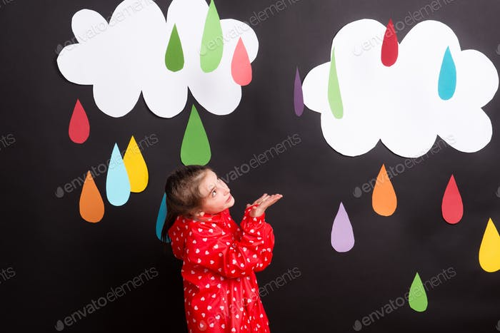 A small girl on a black background with clouds and raindrops.