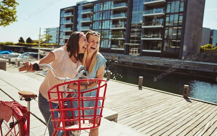 Zwei junge Freundinnen lachen beim Herumlaufen im Sommer