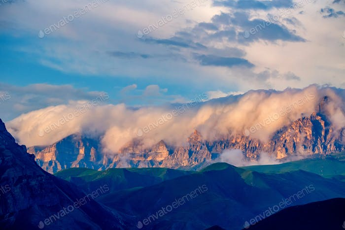 Scenic view of foggy mountains. Sunlit rocks and clouds