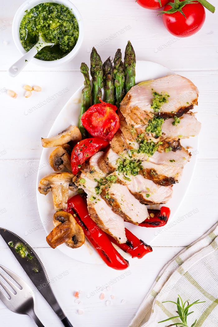 Chicken breast grill with bbq vegetables and pesto sauce in a plate on a wooden background, flat lay