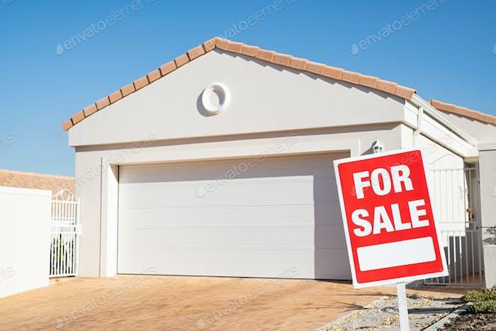 Immobilienhaus mit zum Verkauf Schild