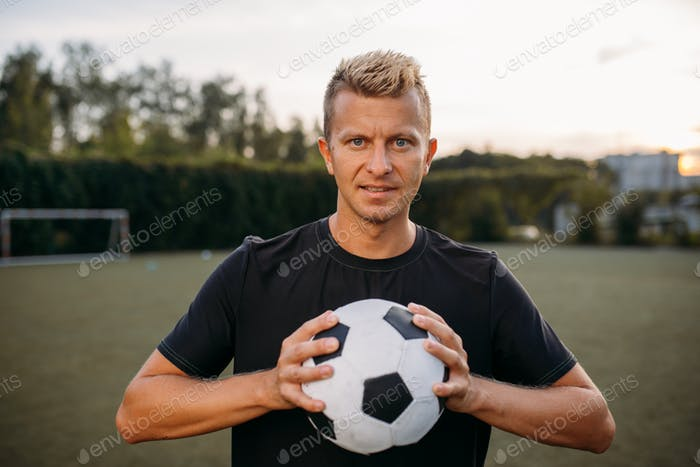Soccer player holding ball in hands on the field