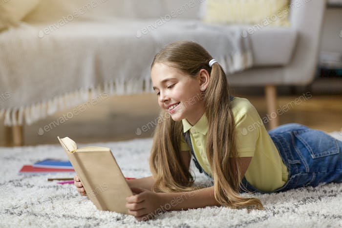 Kid lying on floor carpet, holding and reading book