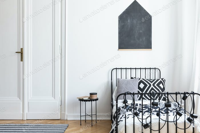 Black poster on white wall above bed in simple bedroom interior