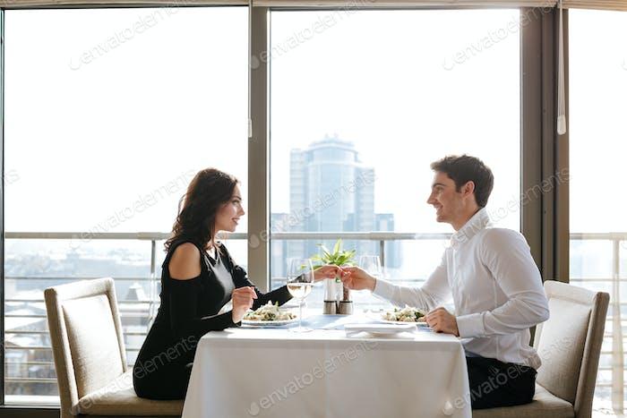 Happy loving couple sitting in restaurant indoors