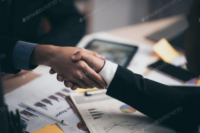 Dos hombre de negocios seguro dándole la mano durante una reunión en la oficina, el éxito, el trato