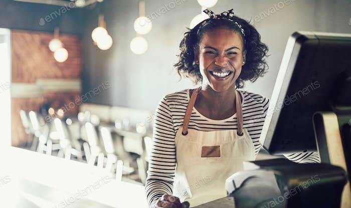 Lachende junge afrikanische Kellnerin arbeitet in einem trendigen Restaurant