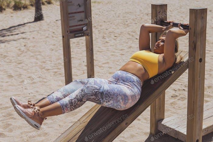 Woman in sportswear training in gym outside