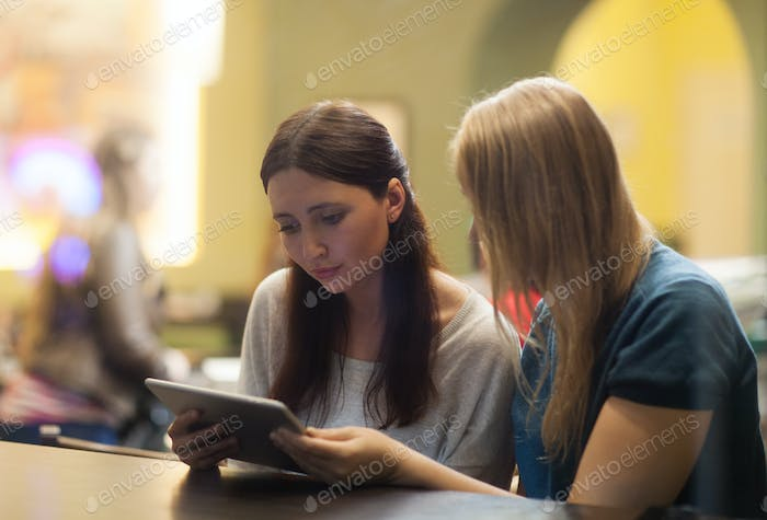 Two women in the restaurant using electronic tablet