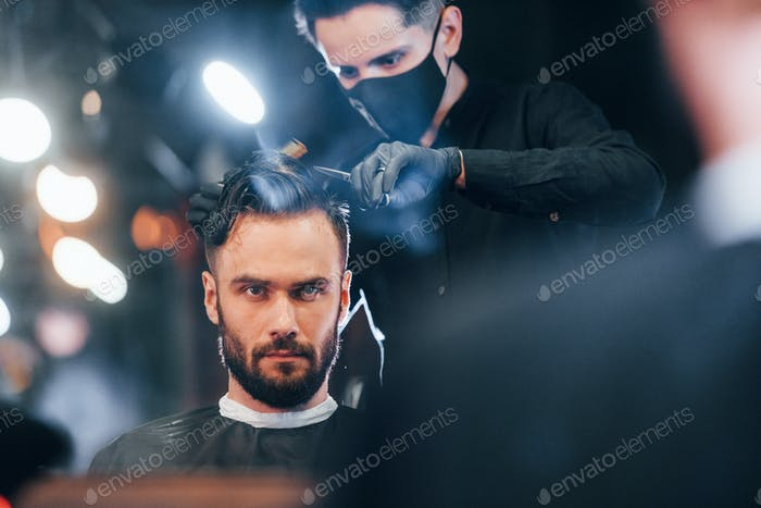 Young stylish man sitting in barbershop