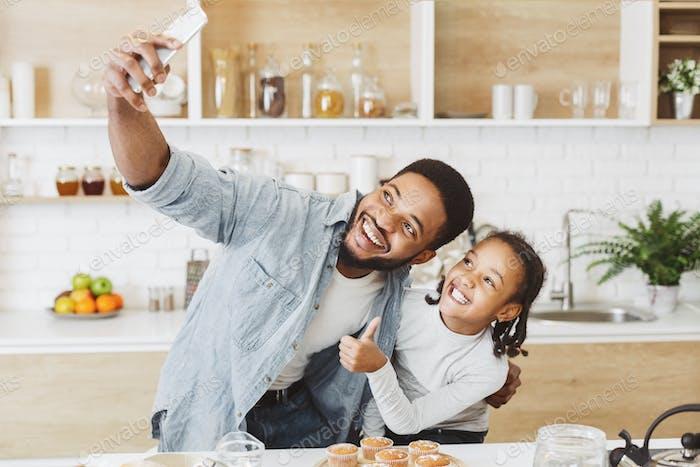 negro papá y hija Encantador selfie en teléfono en Cocina