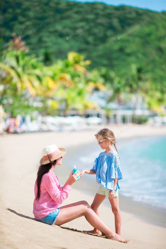 Young mother applying sun cream to kid hand outdoors