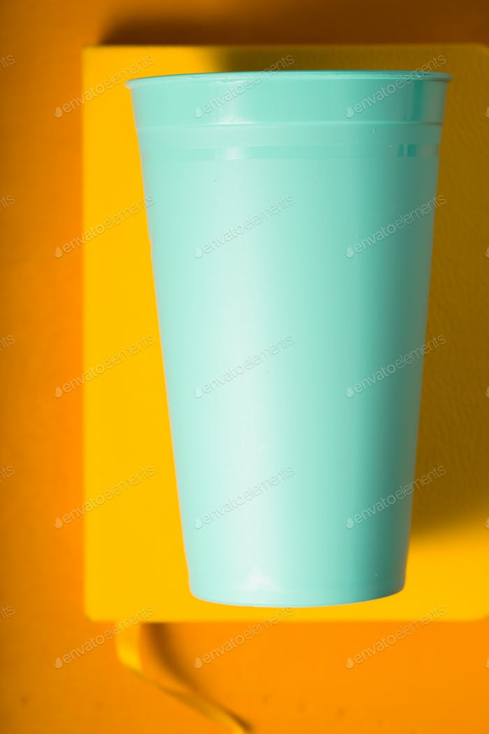 Blue plastic cup on the yellow background