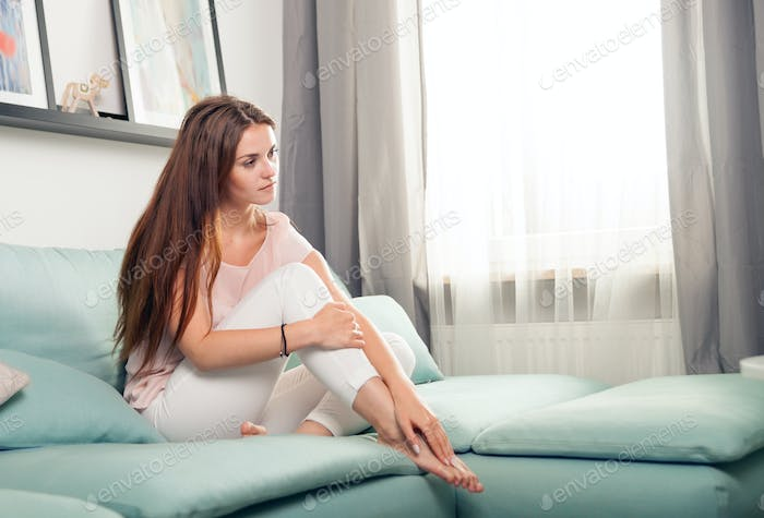 Happy young woman sitting on couch and relaxing at home. Casual style indoor shoot