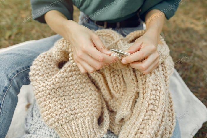Girl sitting in a summer park and knitting