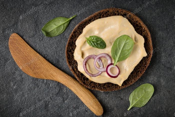 Öffnen Sie Sandwich mit Hummus. Draufsicht, flach gelegt.