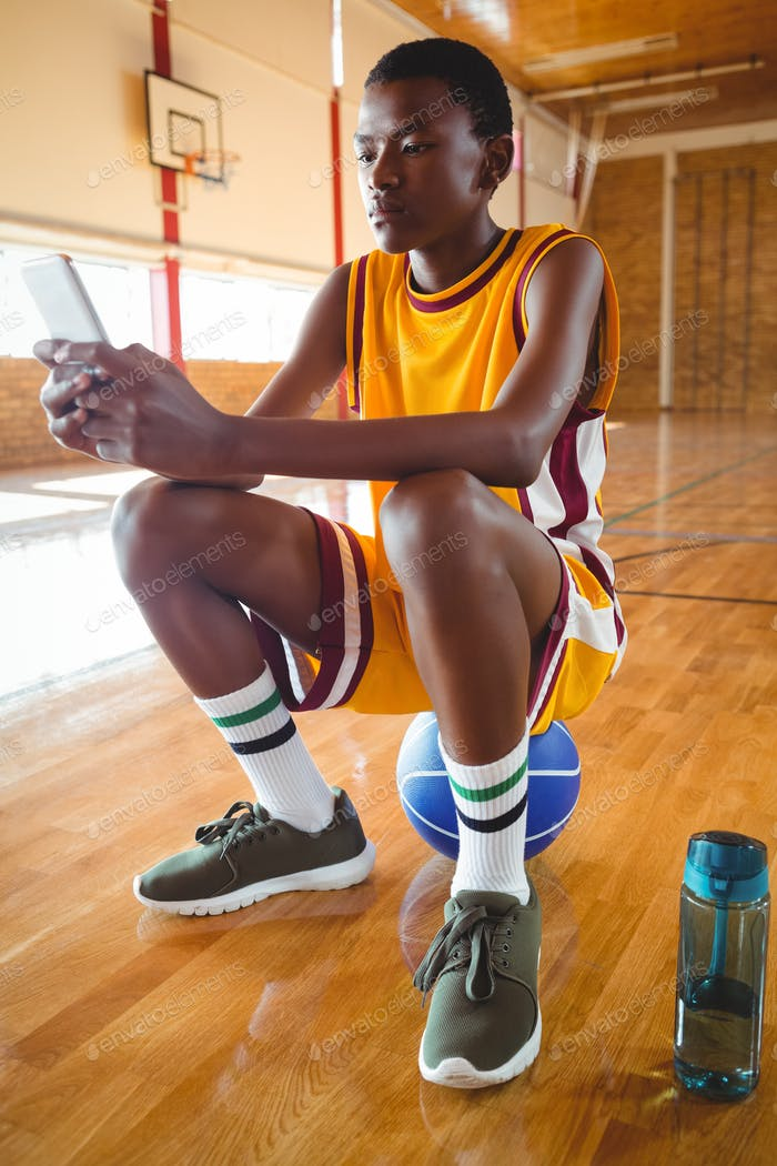 Teenage boy using mobile phone while sitting on ball