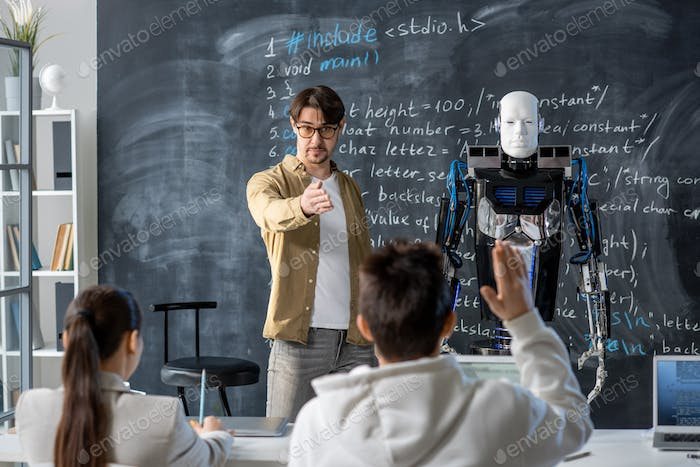 Contemporary teacher pointing at one of students wanting to ask question