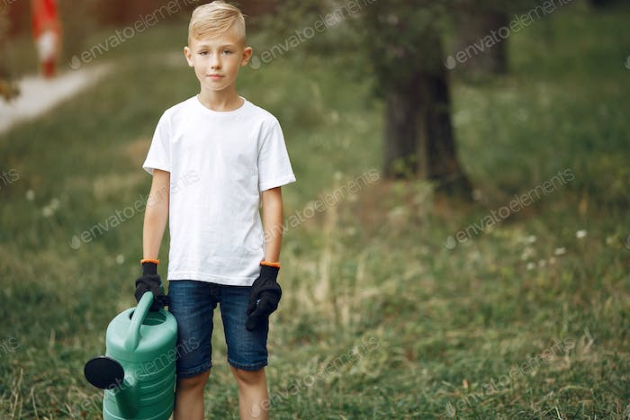 Cute little boy planting a tree on a park