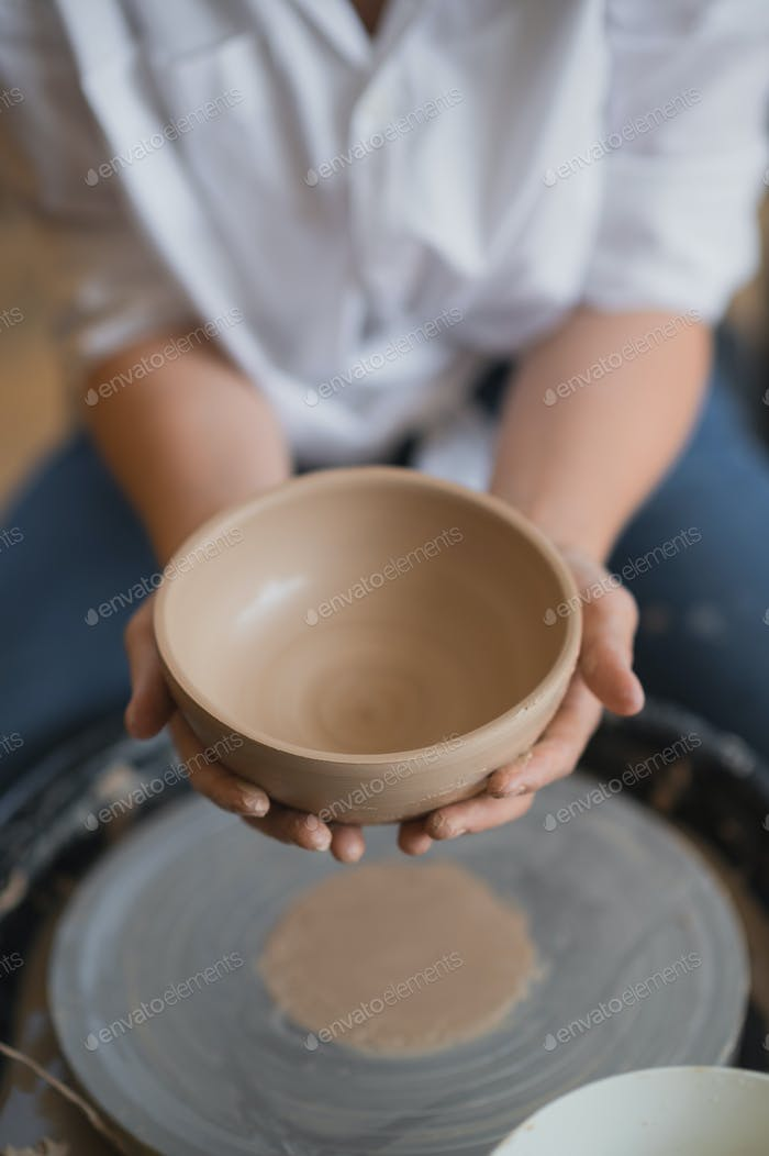 The female potter finished making a clay vase remove it from the potter's wheel. Creating vase