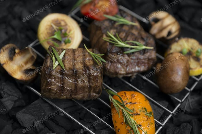 Meat steak with rosemary and mushrooms on grid