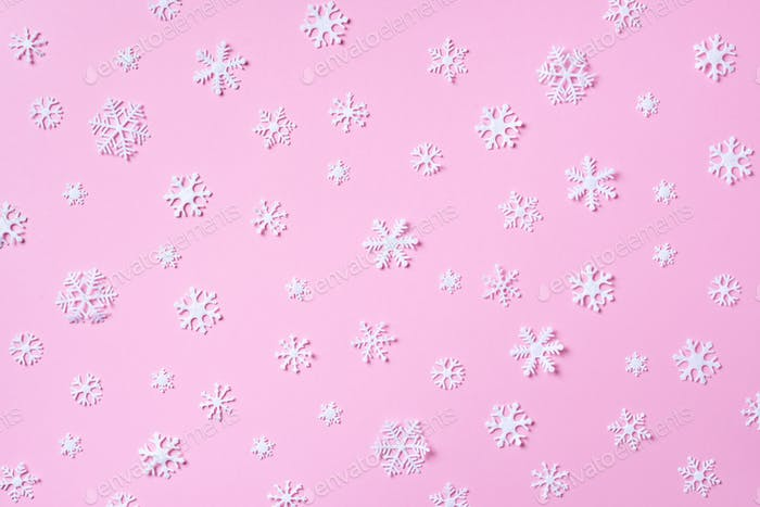 Winter pattern made of white snowflakes on pink background. Top view. Flat lay. Winter composition