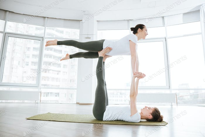 Two attractive young women balancing and doing acro yoga