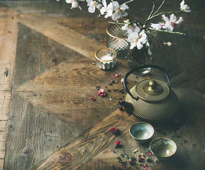 Asian golden iron teapot, cups, candles and almond blossom flowers
