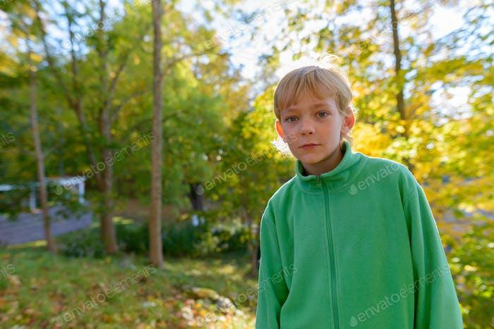 Junge gutaussehende Junge im Park im Herbst