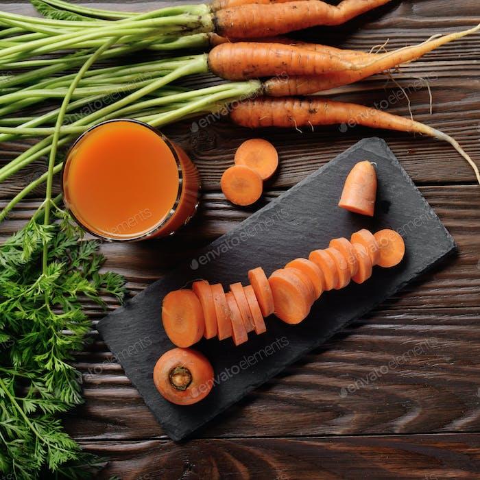 Top view at fresh organic vegetarian Carrot juice on wooden kitc